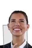 Fermez-vous de la femme d'affaires de sourire recherchant tout en employant l'interface en verre photos stock