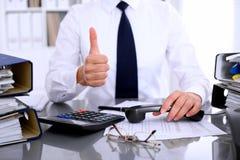 Fermez-vous de la femme d'affaires montrant le signe correct tout en rédigeant le rapport, en calculant ou en vérifiant l'équilib Images stock