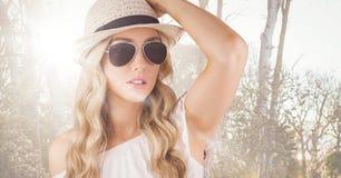 Fermez-vous de la femme dans des vêtements d'été contre les arbres troubles avec la fusée Image stock