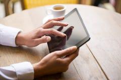 Fermez-vous de la femme de mains à l'aide de son PC de comprimé dans le restaurant photo stock