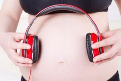 Fermez-vous de la femme enceinte avec des écouteurs sur le listenin de ventre photos libres de droits
