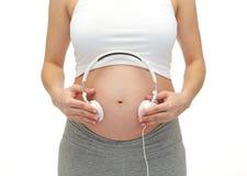 Fermez-vous de la femme enceinte et des écouteurs sur le ventre Photographie stock libre de droits