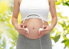Fermez-vous de la femme enceinte et des écouteurs sur le ventre Photographie stock