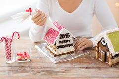 Fermez-vous de la femme faisant des maisons de pain d'épice Photographie stock libre de droits