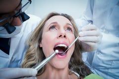 Fermez-vous de la femme faisant examiner ses dents image stock