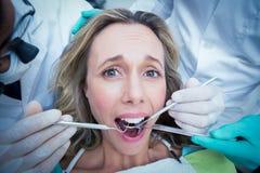 Fermez-vous de la femme faisant examiner ses dents photographie stock