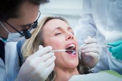 Fermez-vous de la femme faisant examiner ses dents photo stock