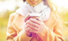 Fermez-vous de la femme heureuse avec du café en parc d'automne Photographie stock