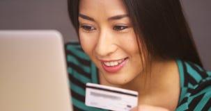 Fermez-vous de la femme japonaise souriant avec la carte de crédit photo libre de droits