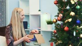 Fermez-vous de la femme joyeuse accroche des jouets sur l'arbre de Noël les prenant de la boîte banque de vidéos