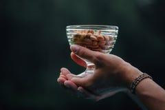 Fermez-vous de la femme jugeant le bol en verre avec des amandes nuts photos stock