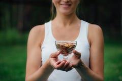Fermez-vous de la femme jugeant le bol en verre avec des amandes nuts image libre de droits