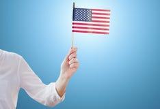 Fermez-vous de la femme jugeant le drapeau américain disponible Photographie stock libre de droits