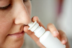 Fermez-vous de la femme malade à l'aide de la pulvérisation nasale photos libres de droits
