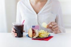 Fermez-vous de la femme mangeant des puces, du hot-dog et du kola Photographie stock libre de droits
