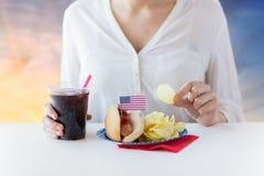 Fermez-vous de la femme mangeant le hot-dog avec le kola Photos libres de droits