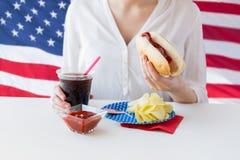 Fermez-vous de la femme mangeant le hot-dog avec le coca-cola Images stock