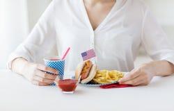Fermez-vous de la femme mangeant le hot dog et les pommes frites Image libre de droits