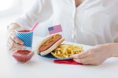 Fermez-vous de la femme mangeant le hot dog et les pommes frites Images libres de droits