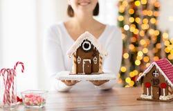 Fermez-vous de la femme montrant la maison de pain d'épice Photo libre de droits