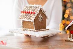 Fermez-vous de la femme montrant la maison de pain d'épice Images libres de droits