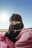 Fermez-vous de la femme musulmane asiatique prête à tirer une flèche Image stock