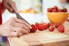 Fermez-vous de la femme préparant la salade de fruits Images stock