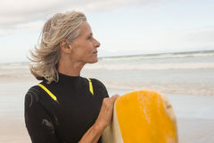 Fermez-vous de la femme semblant partie tout en portant la planche de surf Image stock