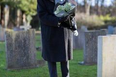 Fermez-vous de la femme supérieure avec des fleurs se tenant prêt la tombe Image stock