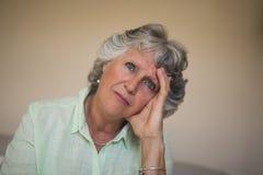 Fermez-vous de la femme supérieure réfléchie triste à la maison photos stock
