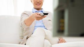 Fermez-vous de la femme supérieure heureuse regardant la TV à la maison Image libre de droits