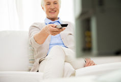 Fermez-vous de la femme supérieure heureuse regardant la TV à la maison Photos libres de droits
