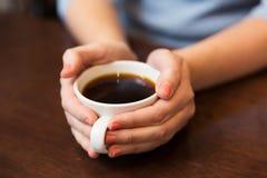 Fermez-vous de la femme tenant la tasse de café noir chaude image libre de droits