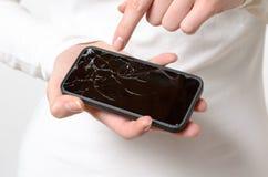 Fermez-vous de la femme tenant le téléphone portable cassé Photo libre de droits