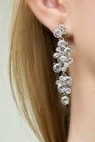 Fermez-vous de la femme utilisant les boucles d'oreille brillantes de diamant Photo stock