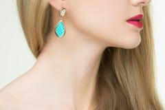Fermez-vous de la femme utilisant les boucles d'oreille brillantes de diamant Images stock