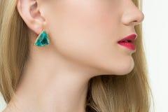 Fermez-vous de la femme utilisant les boucles d'oreille brillantes de diamant Photographie stock libre de droits