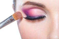 Fermez-vous de la fille appliquant le maquillage lumineux Photographie stock