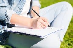 Fermez-vous de la fille avec l'écriture de carnet en parc Image libre de droits