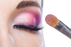 Fermez-vous de la fille avec l'oeil fermé appliquant le maquillage Photographie stock libre de droits