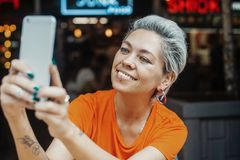 Fermez-vous de la fille blonde attirante dans le T-shirt orange faisant le selfie au café image libre de droits