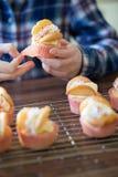 Fermez-vous de la fille dans la cuisine mangeant les gâteaux à la maison faits de tasse Images stock
