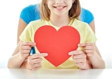 Fermez-vous de la fille et de la mère tenant le coeur rouge Images stock