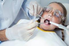 Fermez-vous de la fille faisant examiner ses dents photos stock