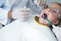 Fermez-vous de la fille faisant examiner ses dents image stock