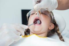 Fermez-vous de la fille faisant examiner ses dents image libre de droits