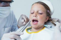 Fermez-vous de la fille faisant examiner ses dents photo stock