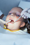 Fermez-vous de la fille faisant examiner ses dents photo libre de droits