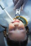 Fermez-vous de la fille faisant examiner ses dents photos libres de droits