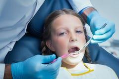 Fermez-vous de la fille faisant examiner ses dents photographie stock libre de droits